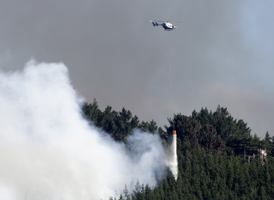 A helicopter dumps water on the fire.