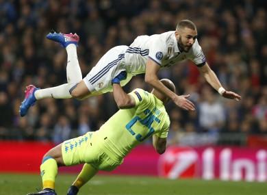 Real Madrid's Karim Benzema jumps over Napoli goalkeeper Pepe Reina.