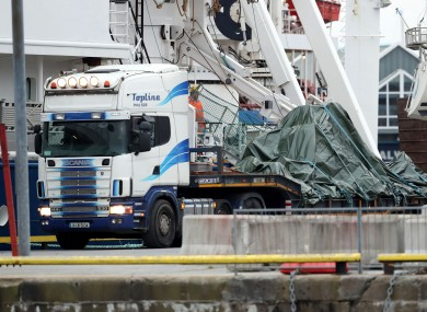 A flatbed truck carrying the wreckage of Rescue 116.