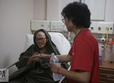 A family member gives water to Taiwanese man Liang Sheng-yueh at the Grande Hospital in Kathmandu, Nepal.