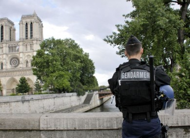 A police officer stands near the entrance of Notre Dame cathedral in Paris on Tuesday