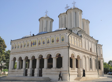 A priest walks outside the Romanian Patriarchal Cathedral in Bucharest.