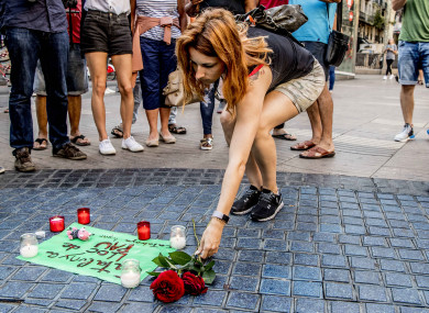 People lay flowers and candlelights in Las Ramblas avenue a day after the deadly van attack in Barcelona.