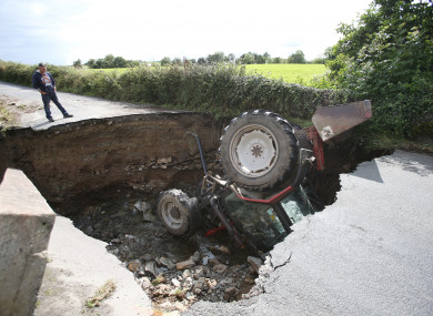 A man looks at a tractor which has fallen into a road collapsed in Iskaheen, County Donegal.
