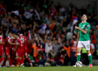 Robbie Brady looking devastated as Serbia celebrate their goal.