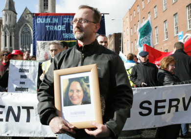 Conor Mac Liam holds a picture of his wife Susie Long at a demonstration in Dublin.