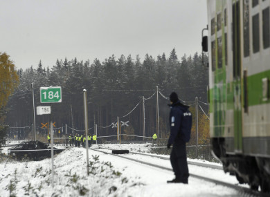 Rescue, military personnel and a policeman gather at the railroad crossing of the crash.