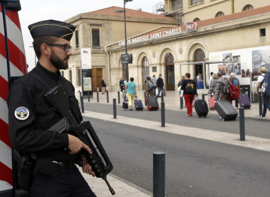 A police officer stands guard while passengers enter the Marseille Saint Charles train station, a day after a man fatally stabbed two women outside the train station.
