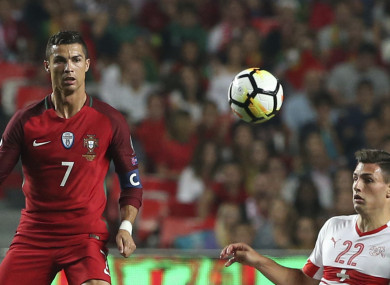 Portugal's Cristiano Ronaldo, left, challenges for the ball with Switzerland's Fabian Schar.