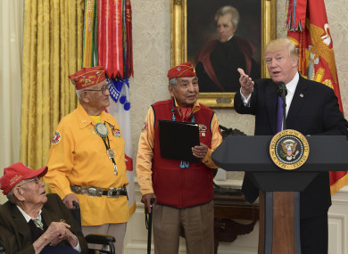 President Donald Trump, right, speaks during a meeting with Navajo Code Talkers including Fleming Begaye Sr, seated left, Thomas Begay, second from left, and Peter MacDonald, second from right, in the Oval Office.
