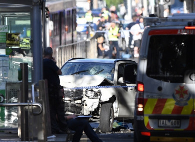A damaged vehicle is seen at the scene of an incident on Flinders Street