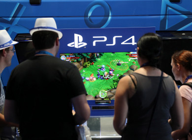 Visitors play Sony's Playstation 4 at Gamescom in Cologne.