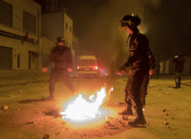 Riot police hold their positions near a fire after clashes with demonstrators in Tebourba, south of the Tunisian capital Tunis earlier this week.