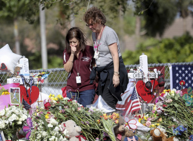 Margarita Lasalle, a bookeeper and Joellen Berman, a guidance data specialist look at the memorial after returning to the school.