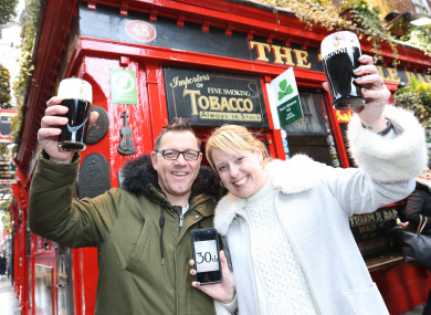 Jenna and Mark Durrant from England raising a pint outside the Temple Bar pub.