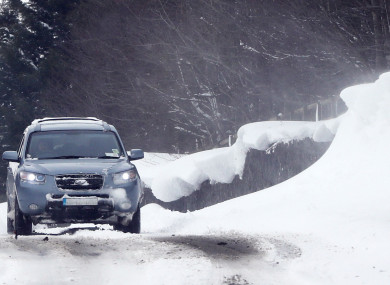 A car passing snow drifts at the Curragh in Kildare yesterday.