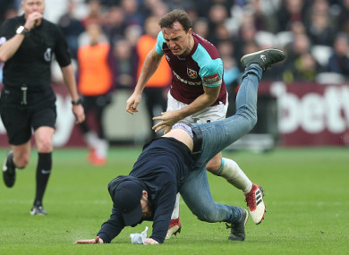 Mark Noble of West Ham fights with a pitch invader protesting the board of directors during the Premier League match between West Ham United and Burnley at London Stadium earlier this month.