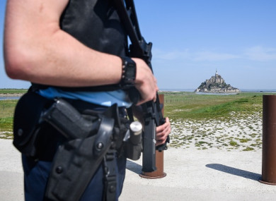 An armed officer stands by the road leading to Mont Saint-Michel after it was evacuated today