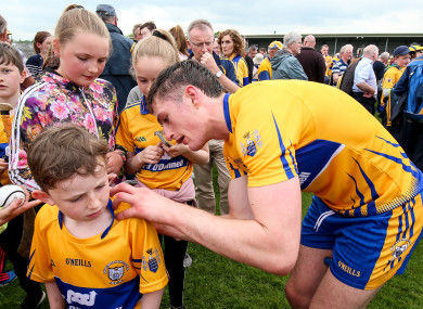 Conor Cleary signs an autograph for a young fan at full-time.