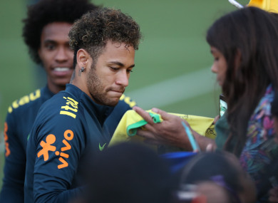 Brazil's Neymar (L) signs for fans after a training session of the Brazilian national soccer team.