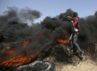 Palestinians hurl stones and burn tires near the fence of the Gaza Strip's border with Israel, during a protest east of Khan Younis, in the Gaza Strip.