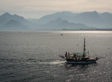 A tourist ship sails in front of a mountain landscape near Antalya, a major summer destination for tourism along Turkey's Mediterranean coast.