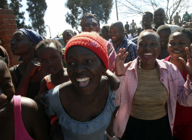 Women sing and dance after seeing former Zimbabwean Leader President Robert Mugabe at a polling station in Harare, Zimbabwe.