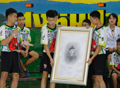 The boys making their first public appearance, holding a photo of the volunteer diver who died during their rescue.