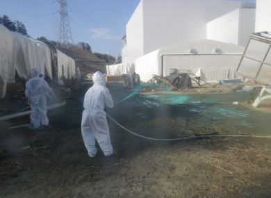 Workers wearing protective suits spray adhesive synthetic resin over the ground at the Tokyo Electric Power Co. (TEPCO)'s Fukushima Daiichi Nuclear Power Plant