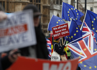 Pro and anti Brexit demonstrators wave their placards and flags outside the Houses of Parliament in London