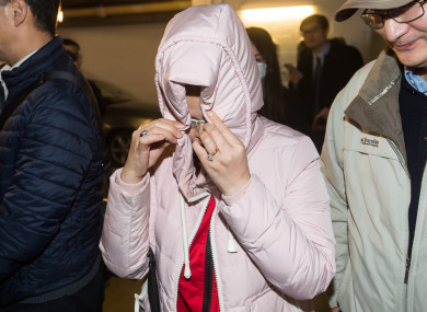 A woman hides her face while leaving British Columbia Supreme Court, in Vancouver on Tuesday