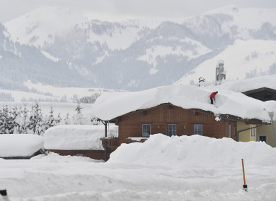 A man cleans snow from a roof on Saturday in St. Jakob in the Austrian province of Tyrol.