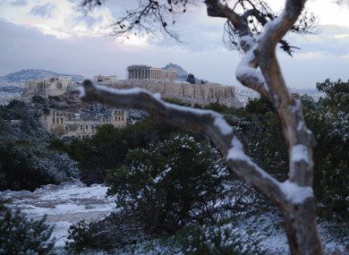 Snow covers a tree in front of the ancient Acropolis hill with the 500BC Parthenon temple