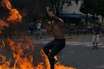 A demonstrator with a gas mask jumps over fire amid collisions with security forces in Caracas yesterday.