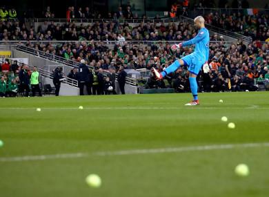 Darren Randolph removes tennis balls from the field.