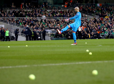 Darren Randolph removes tennis balls from the pitch.