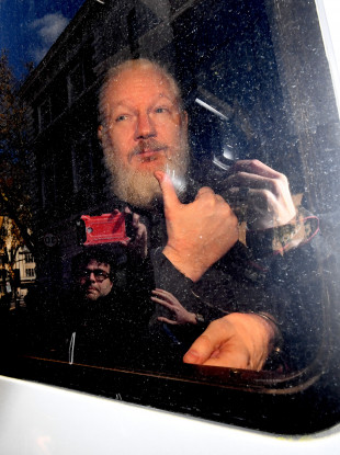 Julian Assange arrives at Westminster Magistrates' Court in London yesterday