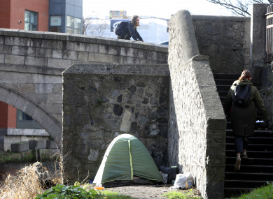 A woman walks past a homeless tent iunder a bridge in Dublin earlier this year.