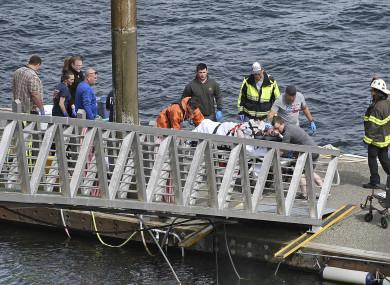 Emergency response crews transport an injured passenger to an ambulance