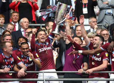 Villa captain Jack Grealish lifts the play-off final trophy alongside his team-mates.