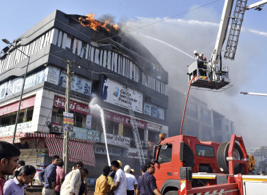 Firefighters work to douse flames on a building in Surat.