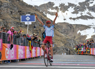 Zakarin celebrates while crossing the finish line to win the 13th stage.