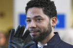 Jussie Smollett waves as he leaves Cook County Court.