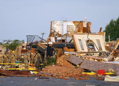 Workers look through tornado damage at the American Budget Value Inn in El Reno