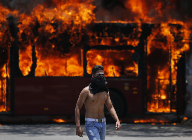 An anti-government protester walks near a bus that was set on fire by opponents of Venezuela's President Nicolas Maduro yesterday