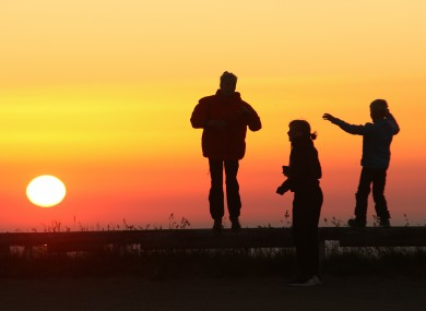 People watch the sunrise this morning on the mountain Brocken in Schiere, Germany,