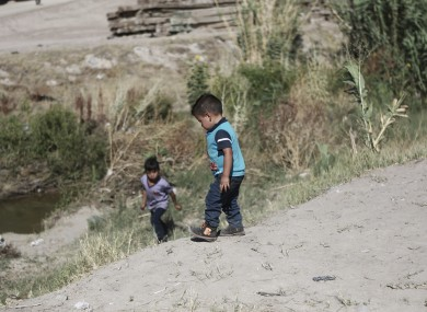 Migrant children wait for their father on the Mexican side of the Rio Bravo before crossing the US-Mexico border.
