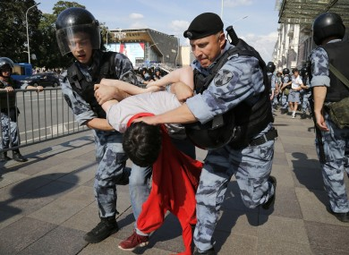 Police officers detaining a man during today's rally in Moscow