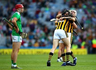 Dejection for Limerick's Barry Nash as Kilkenny players celebrate victory.