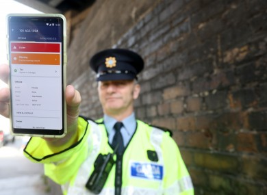 Garda from the National Road Policing unit Mark Murphy holds a mobile phone during a the Road Safety Authority (RSA) as they publish a road safety progress review.